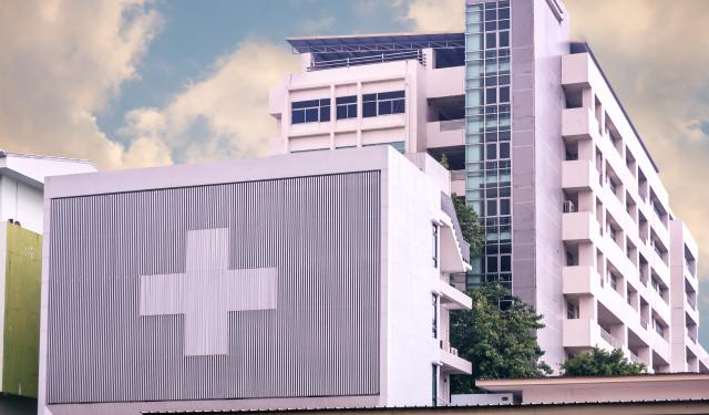 Concrete hospital building with medical cross