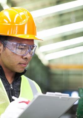 Man wearing hard hat and safety goggles holding clipboard