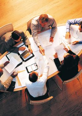 Group of business people sitting at a large table reviewing paperwork with two of the people shaking hands over the table