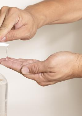 Close-up image of someone pumping hand sanitizer into their hands from a clear bottle