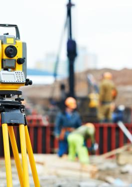 A theodolite in focus with people in the distance working and viewing the area.