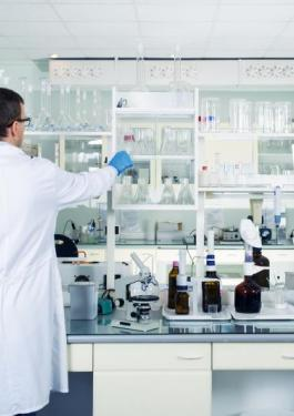 Lab worker standing in front of work space with lab equipment and supplies
