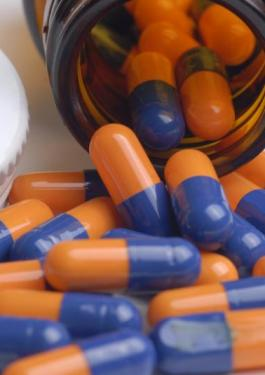 Orange and blue pills spilling out of a bottle