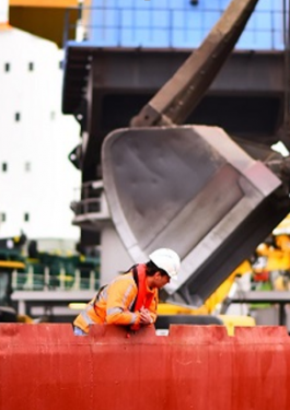 Woman in PPE at a loading site leaning over an orange barrier and looking down