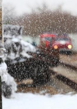 Blurred image of workers and first responders at a train track during snowfall
