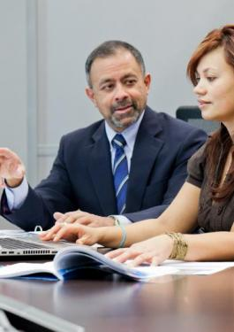 Two business people having a discussion while sitting at a table and one of them types on a laptop