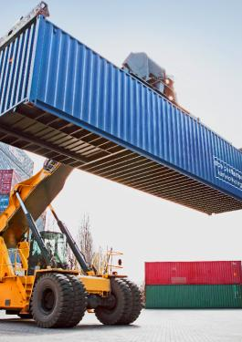 Operator lifting a single shipping container onto a stack of shipping containers