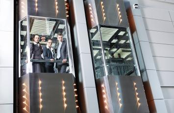 An elevator with three business people peering below through the glass as the use the elevator
