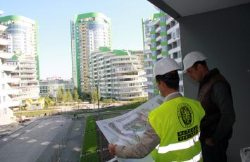 Bureau Veritas employee viewing building plans with someone as they stand outside in front buildings