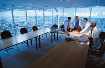 Four businessmen reviewing plans in a conference room overlooking the floor below