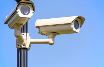 Close up of two security cameras on a pole