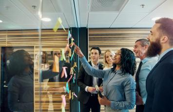 Group of business people reading post it notes on a glass wall