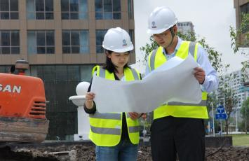 Two Bureau Veritas employees looking at building plans together