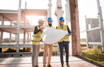 Three people reviewing plans at a client property site