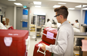 employee carrying red and white cooler